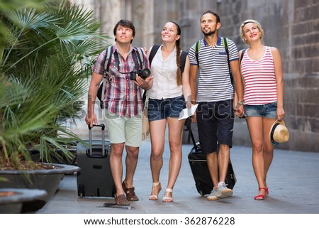 Positive tourists at summer vacation walking the street and smiling - stock photo