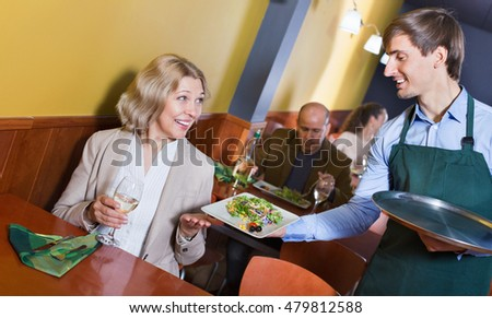 Positive waiter bringing order to mature female in restaurant