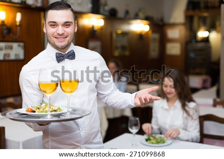 Positive waiter holding tray with glasses of wine in bar  - stock photo