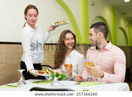 Positive waitress brings prepared meal to visitors table - stock photo
