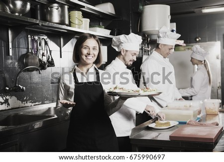 Positive waitress taking order of meal from restaurants kitchen