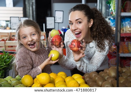 positive woman and beautiful little girl posing whith apples in department fruits of store