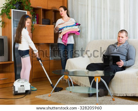 Positive woman and cute girl doing general cleaning, man having rest. Focus on girl - stock photo