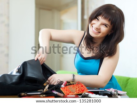 positive woman can not finding anything in her purse at table