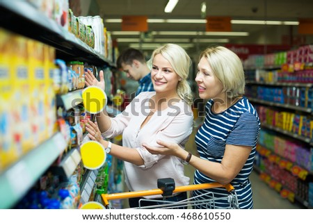Positive woman clients buying infant food in jars at supermarket