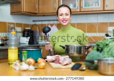 Positive woman cooking soup with meat in domestic kitchen - stock photo