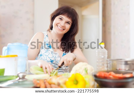 Positive  woman cutting the celery for salad