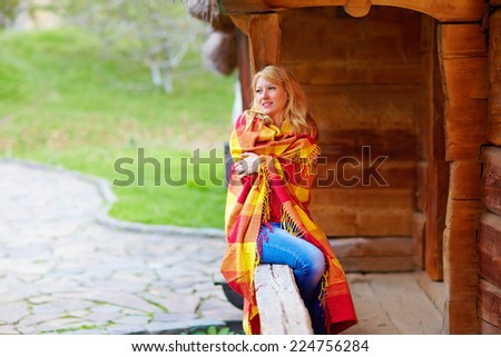 positive woman enjoying autumn, wrapping herself in warm blanket - stock photo