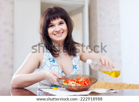 Positive woman pours oil to vegetables salad at home