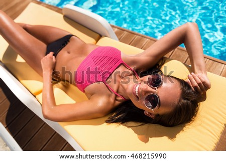 Positive woman resting near swimming pool