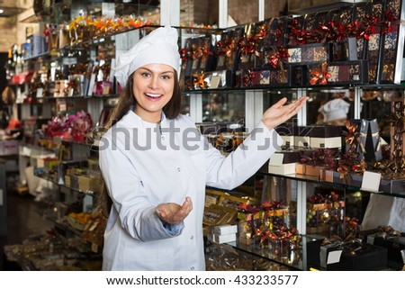 Positive woman selling fine chocolates and confectionery in cafe