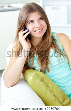 Positive woman talking on phone sitting on a sofa at home