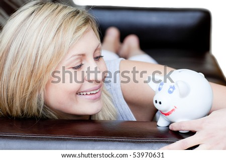 Positive woman using a piggybank against a white background - stock photo