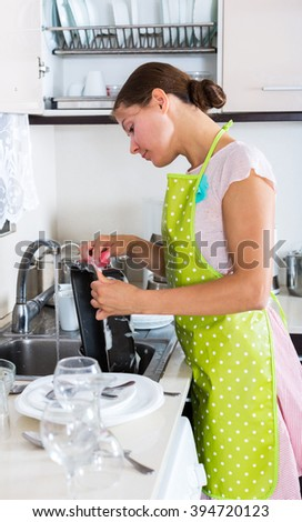 Positive woman washing dishes and baking tray in residential kitchen