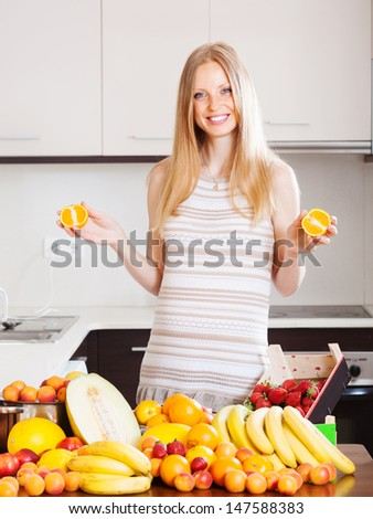 Positive  woman with  oranges and other fruits at kitchen