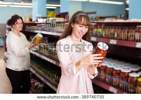 Positive women purchasing pickled vegetables at East-European supermarket