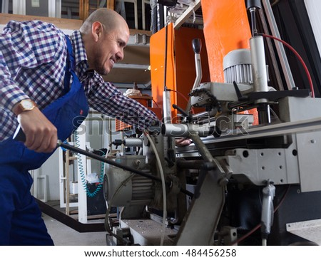 Positive worker near milling machine at factory