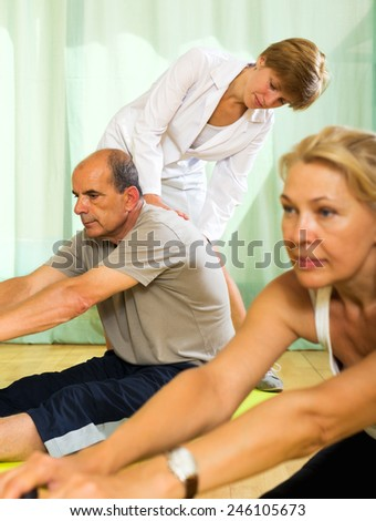Positive yoga instructor showing new asana to mature couple