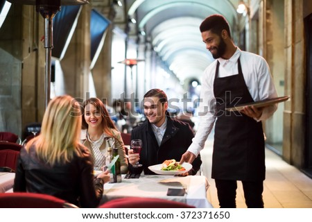Positive young black waiter serving terrace restaurant guests at table.Focus on the man - stock photo