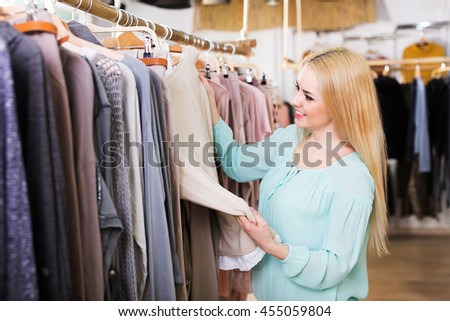 Positive young blonde choosing new blouse in shop