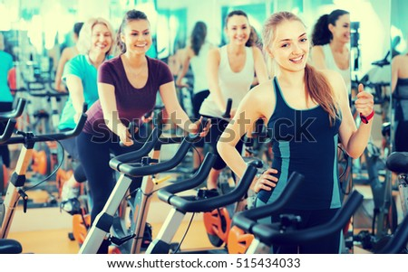 Positive young blonde woman posing in modern gym for females