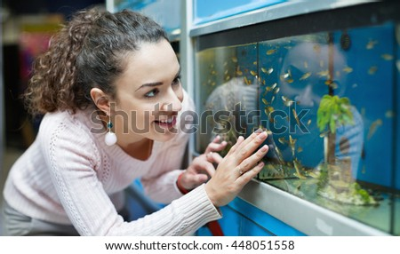 Positive young brunette girl looking at tropical fish in aquarium
