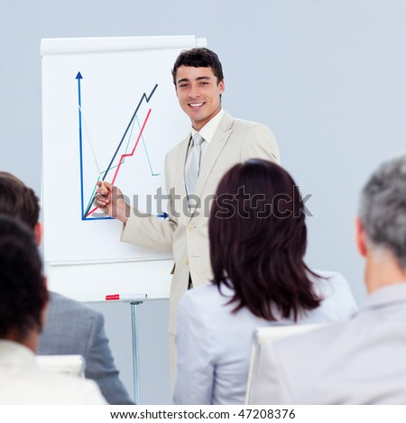 Positive young businessman doing a presentation to his colleagues