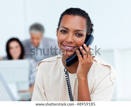 Positive young businesswoman talking on phone at work