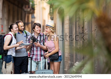 Positive young company of impressed travelers during city walking - stock photo