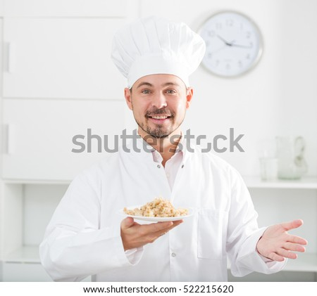 Positive young cook holding plate with porridge at his workplace
