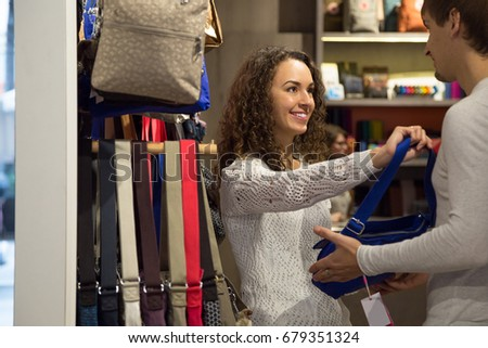 Positive Young couple customers looking at stylish female handbags in store