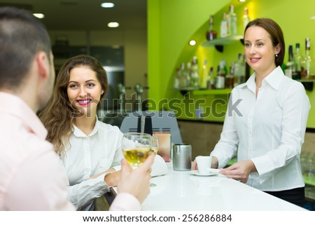 Positive young couple having a date with wine at bar. Focus on girl - stock photo