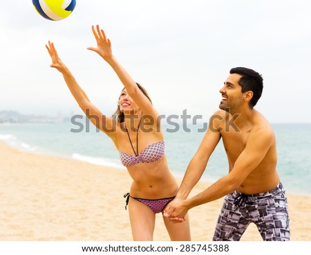 Positive young couple playing volleyball on the beach. Focus on the man - stock photo