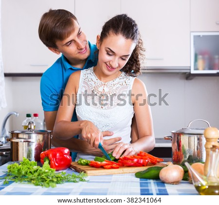 Positive young family couple cooking vegetables in domestic kitchen