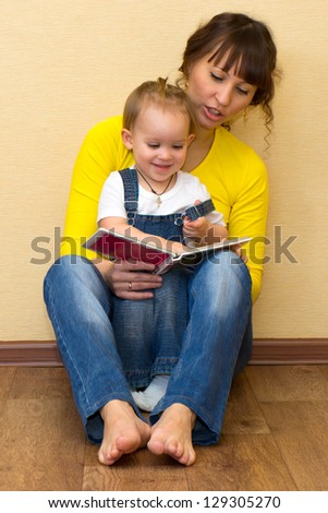 Positive young family reading a book on the floor - stock photo