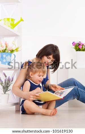 Positive young family reading a book on the floor in the living-room - stock photo
