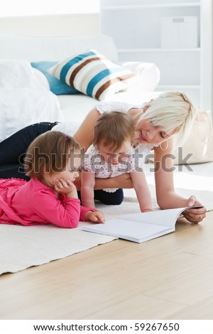 Positive young family reading a book on the floor in the living-room