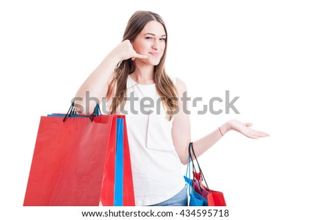 Positive young girl on shopping making a call gesture with hand and carrying shopping bags isolated on white background - stock photo