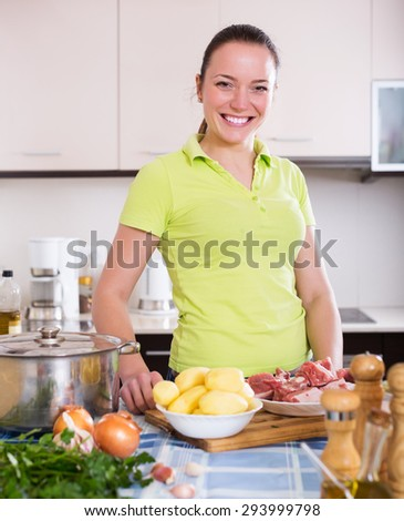 Positive young houswife cooking soup with meat and vegetables at home