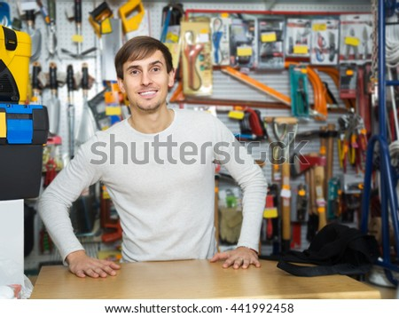 Positive young male seller posing at tooling section of household store