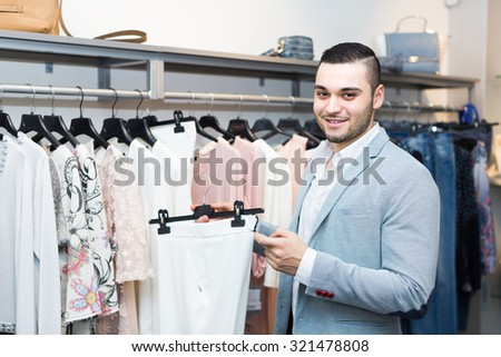 Positive young man buying clothes for his girlfriend at boutique