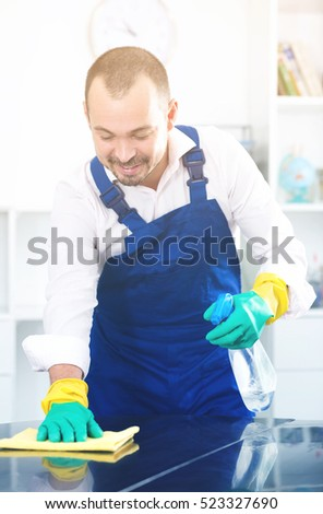 Positive young man in apron cleaning his office desk by cleanser