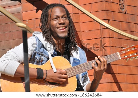 positive young man playing classic guitar on the street - stock photo