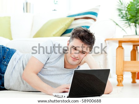Positive young man using his laptop lying on the floor at home - stock photo
