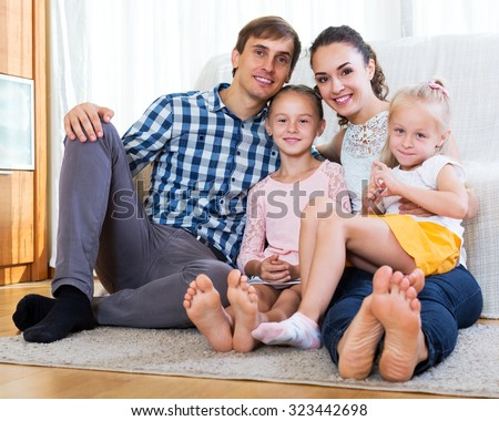 Positive young parents with two daughters relaxing at home - stock photo