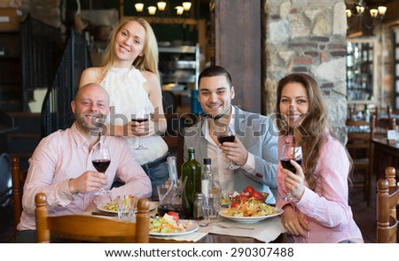 Positive young people enjoying the food and smiling in tavern  - stock photo