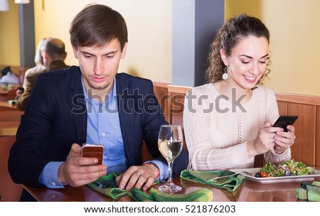 Positive young spouses sitting at restaurant table with smartphones. focus on woman