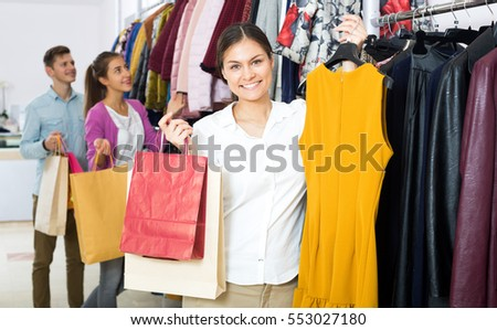 Positive young woman customers chooses liked things in the boutique