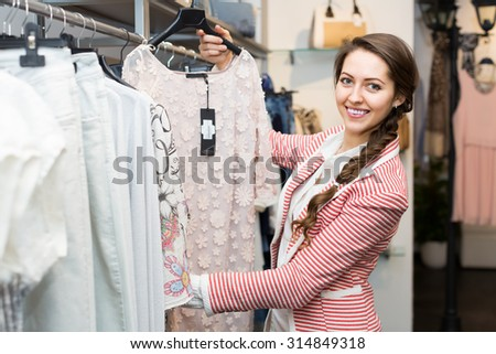 Positive young woman doing shopping at boutique  - stock photo