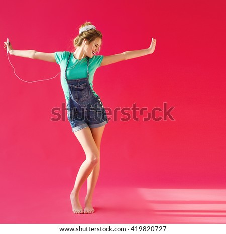Positive young woman listening to music from her phone and dancing